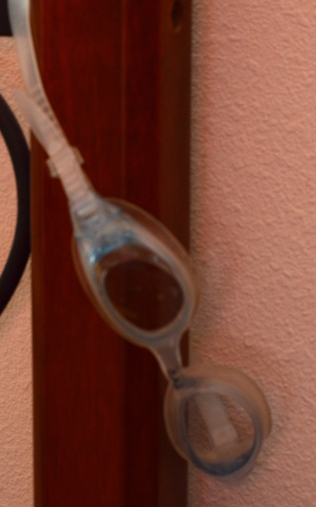 Swim goggles hanging from bedpost.