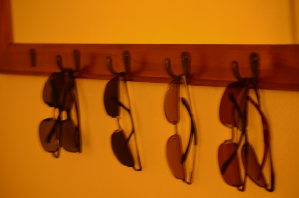 Mirror with sunglasses on hooks.